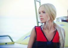 Eine zarte schöne blonde Frau auf einem Schneider trägt eine Schwimmweste leicht und hell auf einer Seekreuzfahrt, einem Rest und Stockbilder