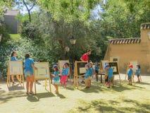 Eine zeichnende Lektion im Freien f?r eine Gruppe Kinder von drei bis sechs Jahre alt Spanisches Dorf Park-Museum lizenzfreie stockbilder