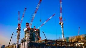Eine Zeitspanne von beweglichen Kränen am im Bau in breiter geschossener Neigung Tokyos stock video footage