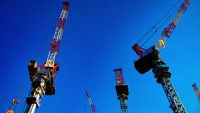 Eine Zeitspanne von beweglichen Kr?nen hinter dem blauen Himmel in breiter geschossener Neigung Tokyos stock footage