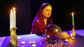 Eine Zigeunerin in einem roten Kleid in den Zimmerbeleuchtungskerzen einer Weissagung auf einer Tabelle stock video
