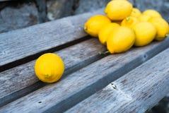 Eine Zitrone auf Holzbank und Gruppe Zitronen hinten Stockfotografie