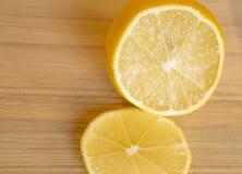 Eine Zitrone geschnitten auf Holztisch Lizenzfreie Stockfotos