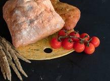 Eine Zusammensetzung des Gemüses und des Brotes in einer rustikalen Art auf einem schwarzen Holztisch Brottomatengurke stockbilder