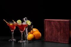 Eine Zusammensetzung von zwei roten Cocktails, ein Haufen von natürlichen Orangen und ein Metallschüttel-apparat auf einem schwar Stockfotografie
