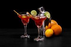 Eine Zusammensetzung von zwei roten Cocktails, ein Haufen von natürlichen Orangen und ein Metallschüttel-apparat auf einem schwar Lizenzfreies Stockfoto