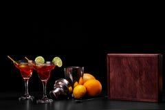 Eine Zusammensetzung von zwei roten Cocktails, ein Haufen von natürlichen Orangen und ein Metallschüttel-apparat auf einem schwar Stockfoto