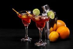 Eine Zusammensetzung von zwei roten Cocktails, ein Haufen von natürlichen Orangen und ein Metallschüttel-apparat auf einem schwar Lizenzfreie Stockfotografie