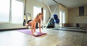 In einem aeroben Studiofrauenüben ausdehnende Übungen unter Verwendung Bügel TRX zu helfen, die Beine auszudehnen härter und
