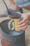 In einem Becher gießen Sie Kaffee vom Topf Stockfotos