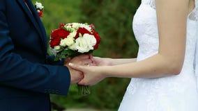 An einem Hochzeitstag streicht der Bräutigam die Braut ` s Hand, den Hochzeitsblumenstrauß stock footage