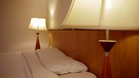 In einem Hotelzimmer mit einer Lampe und einem Doppelbett stock footage