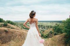 Einem jungen Mädchen, der Braut in einem Hochzeitskleid, wird sie zurück gedreht und anstarrend in den Abstand auf dem Fluss und  Stockfotografie