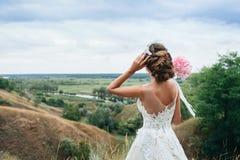 Einem jungen Mädchen, der Braut in einem Hochzeitskleid, wird sie zurück gedreht und anstarrend in den Abstand auf dem Fluss und  Stockbild