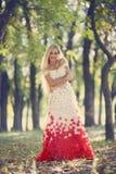 In einem Kleid von rosafarbenen Blumenblättern Stockbild