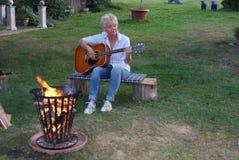 An einem netten Sommerabend mit der Gitarre um das Lagerfeuer stockfotografie