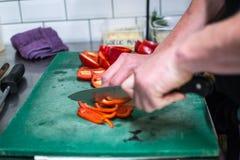 In einem Restaurant kochen, roter Pfeffer mit Messer stockbild