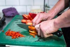 In einem Restaurant kochen, roter Pfeffer mit Messer lizenzfreies stockfoto