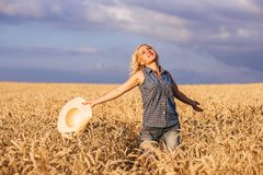 An einem sonnigen Tag geht eine Frau entlang ein Weizenfeld mit einem weißen Kleid, in einem Strohhut auf einem Naturhintergrund  Lizenzfreie Stockfotografie