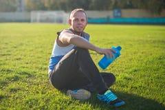 Einen attraktiven Mann zur Schau tragend, der auf Gras und Resten im Stadion sitzt, hält Schüttel-Apparat, sonnigen Tag Stockbild