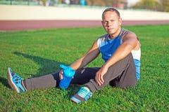 Einen attraktiven Mann zur Schau tragend, der auf Gras und Resten im Stadion sitzt, hält Schüttel-Apparat, sonnigen Tag Stockfotografie