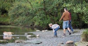 Einen Felsen-werfenden Wettbewerb am See haben stock video footage