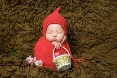 Einen Hut tragend und mit einem Baby schlafend, schaut sehr bequem lizenzfreies stockbild
