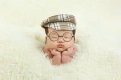 Einen Hut tragend und mit einem Baby schlafend, schaut sehr bequem lizenzfreies stockfoto