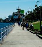 Einen Sommertag durch einen Fluss auf einer Promenade genie?ende und auch fischende Leute stockfotos