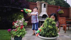 Einen Wasser-Kampf im Garten haben stock video