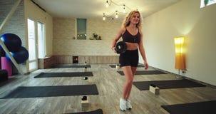 In einer bequemen Sportkleidung nach einer Yogasitzung in einer glücklichen Frau des Wellnessyoga-Studios mit ihrem Sportmattenge stock footage