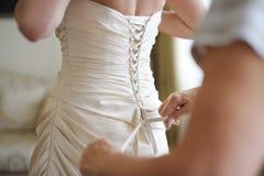 Einer Braut helfen, ihr Hochzeitskleid ein zu setzen stockbild