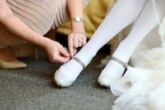 Einer Braut helfen, ihre Hochzeitsschuhe an zu setzen lizenzfreies stockbild