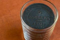 In einer Glasschale eine alte russische Münze auf einem orange Stoffhintergrund Lizenzfreies Stockfoto