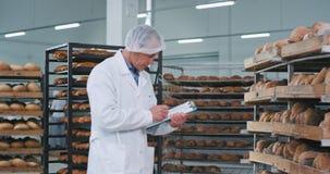 In einer großen Backwarenindustriehauptarbeitskraft, die machen die überprüft, Regale, die vom frischen gebackenen Brot voll sind stock video footage