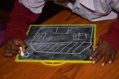 In einer Grundschule wird ein Bild auf einen Schiefer mit Kreide gezeichnet lizenzfreies stockfoto