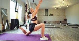 In einer jungen Dame des aeroben Leistungsstudios, die den Körper unter Verwendung Gummibänder TRX ausdehnt, um mehr Sitz und Gla