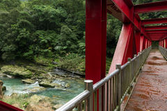 An einer roten Brücke über felsigem Fluss und fruchtbarem Wald Stockbild