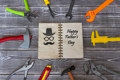 Eines-Tag-alt Notizbuch der Glückwunsch-glücklichen Väter wird durch ein Spielzeugwerkzeug auf einem rustikalen Hintergrund umgeb Stockfotos