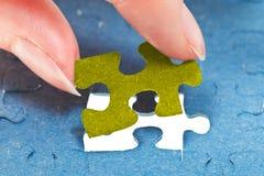 Einfügung des letzten Stückes des Puzzlespiels stockfotografie