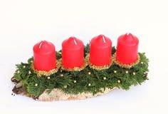 Einführungsspray mit vier roten Kerzen auf Baumscheibe Stockfotografie