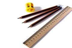 Einfache Bleistifte, Bleistiftspitzer und Machthaber auf einem hellen Hintergrund Stockbild