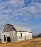 Einfache ergrauende Scheune sitzt auf Feld gegen Hintergrund des Himmels, der Wolken und des goldenen Bodens stockfotografie