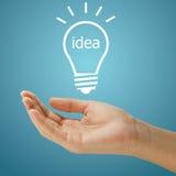 Einfache Glühlampe mit dem Ideenwort, das auf Frauenhand schwimmt Lizenzfreie Stockbilder