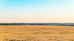 Einfache Landschaft mit einem Roggenfeld und -dorf Lizenzfreie Stockfotos