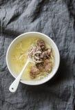 Einfache Rinderbrühe mit Rindfleischfleisch, -zwiebel und -pfeffer auf grauem Hintergrund Gesunde Nahrung, Suppenbasis stockbild