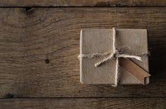 Einfache Schnur gebundener Kasten mit Weinlese-Art-Tag auf altem Eichen-Holz Ta Lizenzfreies Stockfoto