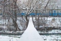Einfache Suspendierungsseilbrücke, die über einem Gebirgsfluss bedeckt mit Schnee mit einem Zug überschreitet auf Winterhintergru Lizenzfreie Stockbilder