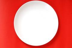 Einfache weiße Platte auf einem roten Hintergrund lizenzfreie stockbilder