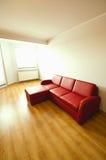 Einfacher Raum mit rotem Sofa Stockbilder